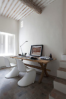 A pair of Verner Panton chairs is pulled up to a simple rustic table to make a home office in this cool corner