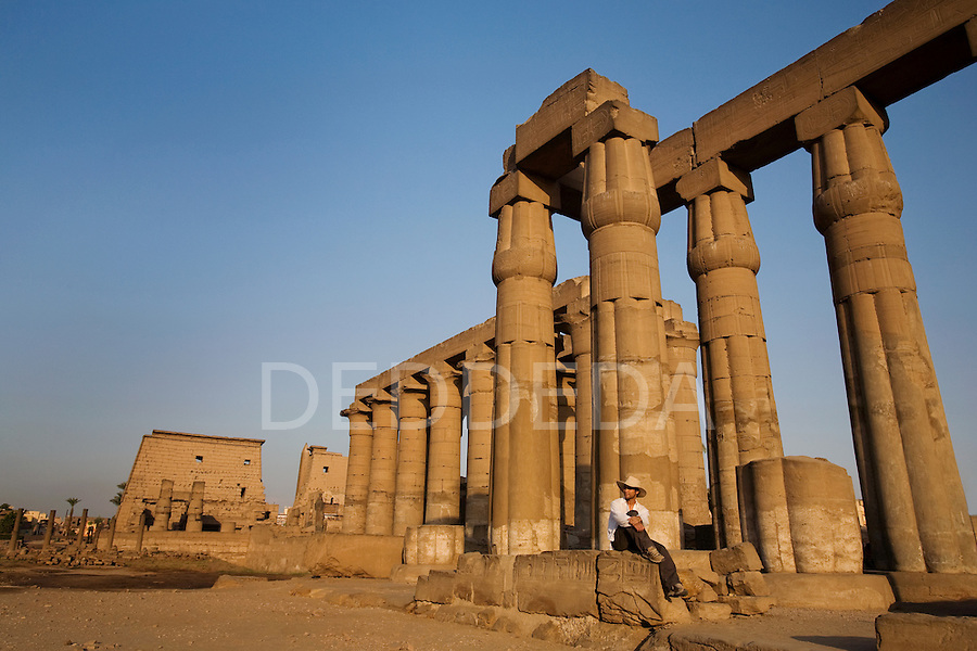 A male tourist wearing a hat visits the Luxor Temple on the East Bank of Luxor, at sunset, along the Nile River, Egypt.