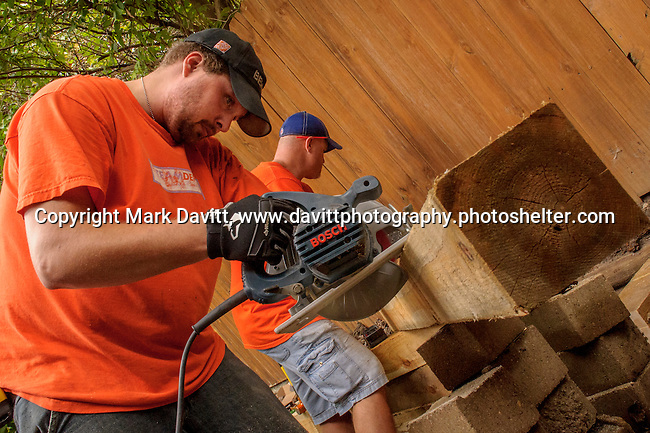 The Bondurant American Legion Post 396 and the Home Depot have partnered together to restore the home U.S. Army veteran of the Korean War, Larry Contri, after undergoing open heart surgery. Volunteer Quade Patton cuts a 6x6 wood post for a retaining wall.