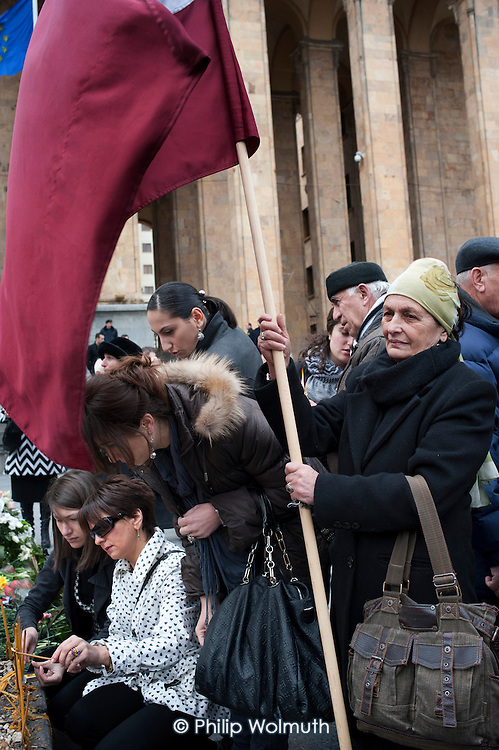 A woman with the pre-Soviet national flag of Georgia at a memorial rally on the anniversary of the 1989 Soviet massacre of 20 hunger strikers outside the Parliament building in Tbilisi, Georgia.