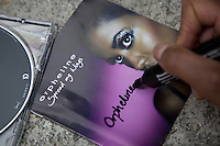 Switzerland. Canton Ticino. Aranno. Orpheline at home signs an autograph on her new realeased musical CD disk. Orpheline is a composer, song writer, a singer and a musician. She is a young woman (24 years old). Her mother is swiss and her father was a black american citizen. Mixed race. Aranno is located in the Malcantone area. 19.03.2010 © 2010 Didier Ruef