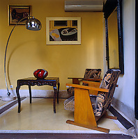 A pair of Art Deco armchairs and an Arco lamp stand in the corner of one of the many living areas located around the riad