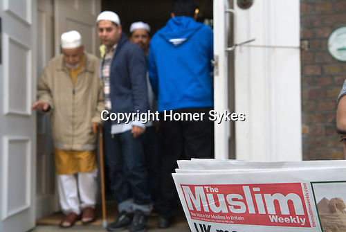 Men leaving Friday Prayers Jamme Masjid Mosque Brick Lane London E1. Man reading a free copy of The Muslim, The Voice of Muslims in Britain, a weekly newspaper distributed outside Mosques after Fridat gatherings.