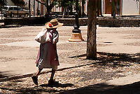 Elderly woman crossing a plaza  in the 19th century mining town of Mineral de Pozos, Guanajuato, Mexico.
