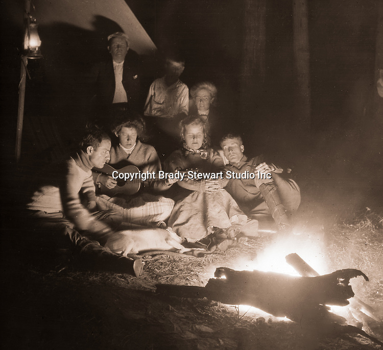 North East PA: Margaret Gray leading the Stewart family in song around the campfire.  Brady Stewart is throwing flash power on the campfire to create an image - 1904.  During the early 1900s, the Stewart family vacationed on Lake Erie near North East Pennsylvania. Since hotels and motels were non-existent, camping was the only viable option for a large number of vacationers.
