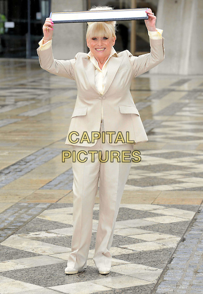 BARBARA WINDSOR.attends a photocall after receiving the Freedom of the City of London at the Guildhall, London, England, UK,.August 4th 2010.full length cream beige suit shirt jacket fringe holding over head raining smiling trousers trouser .CAP/WIZ.©Wizard/Capital Pictures