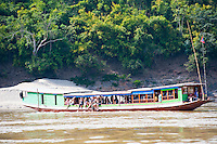 Tourists Sitting on the Slow Boat from Thailand to Vientiane, Laos. The Slow Boat from Huay Xai in North Thailand to Vientiane in Laos takes two days and is a very popular way for tourists to cross the border from Thailand into Laos. The slow boat travels down the Mekong River, stopping off at Pak Beng for one night on the way.