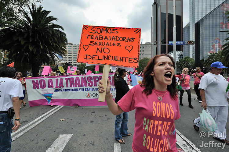 """A sex worker participates in the International March Against Stigma, Discrimination, and Homophobia on August 2 in Mexico City. The march was held on the eve of the XVII International AIDS Conference. The woman's shirt says """"We are part of the solution."""" Her sign reads """"We are sex workers, not delinquents."""""""