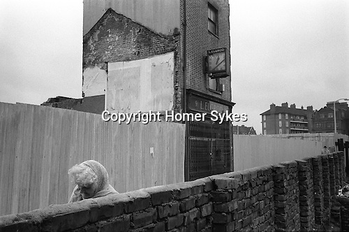 An old lady with head bowed against the cold walks down an ally way from her council flats past one remaining shop,  who's owner has not yet sold out to developers. Whitechapel, east London. England.  1975<br />