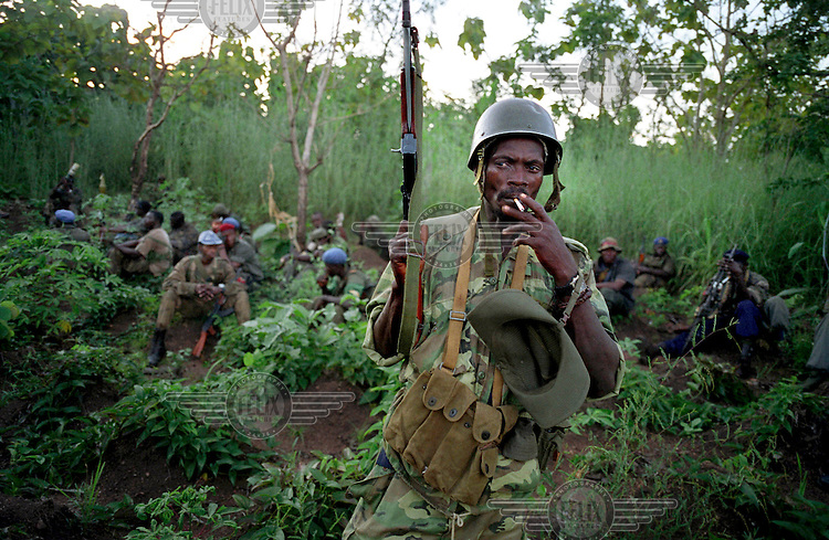 © Sven Torfinn / Panos Pictures..Ivory Coast, near Bouake, October 2002..Three weeks after an uprising by rebel soldiers from the national army, their attempted coup appeared to have failed, but they had taken control of the northern half of the country. Fierce fighting had left hundreds of people dead and up to 150,000 people had become displaced...Rebel troops on patrol in the jungle outside Bouake.