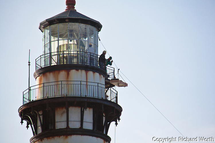 High atop Pigeon Point Lighthouse workmen carefully dismantle the Fresnel lens and sections are moved to the ground by zipline.