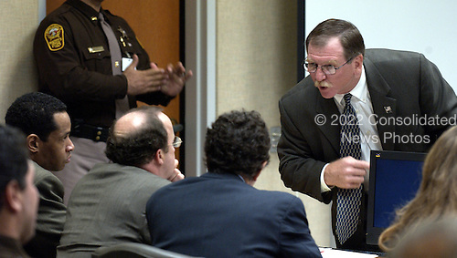 Trial for suspected sniper John Allen Muhammad <br /> Sniper suspect John Allen Muhammad, left, and his defense attorneys Peter Greenspun, seated center, and Jonathan Shapiro, right, listen to Prosecutor Richard Conway during the Muhammad trial at the Virginia Beach Circuit Court in Virginia Beach, Virginia on October 24, 2003. <br /> Credit: Davis Turner - Pool via CNP