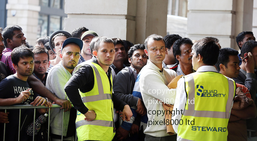 Pic shows: hundred of iPhone lovers queue for new phone today at Apple Store in Covent Garden London.<br /> The majority were of asian or Indian appearance. Perhaps because the iPhone 6 is not launched there until later.<br /> There was quite a lot of pushing and shoving and dozens of yellow jacketed security staff were drafted in to help apple staff. Tempers got heated and times and the security had to step in to keep order.<br /> They also handed out water to keep tempers cool.<br /> <br /> <br /> <br /> <br /> Pic by Gavin Rodgers/Pixel 8000 Ltd