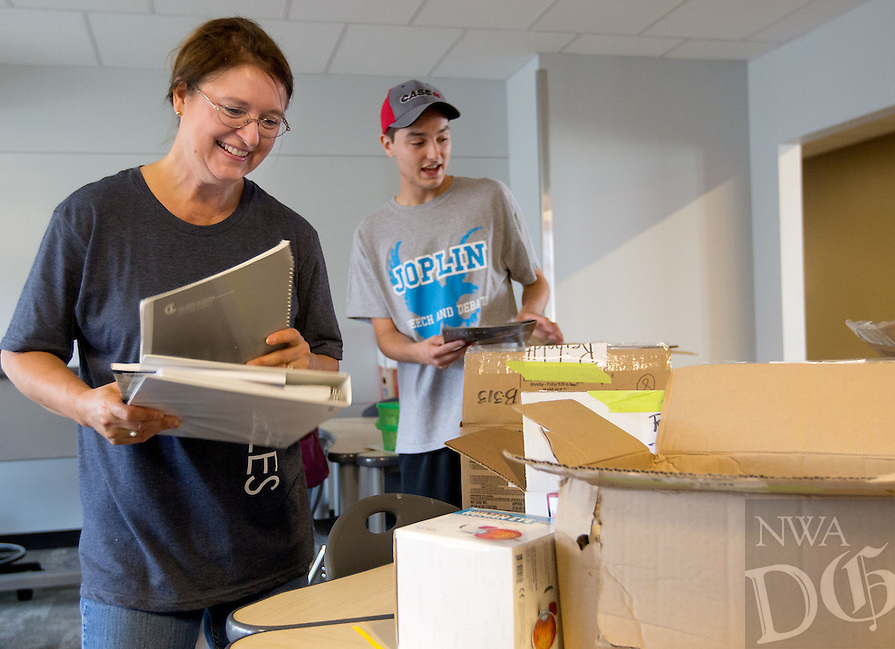 NWA Media/JASON IVESTER --08/21/2014--<br /> Joplin senior Rylee (cq) Harwell (right) helps his former English teacher Kathleen Reiboldt (cq) unpack boxes in her new classroom on Thursday, Aug. 21, 2014, inside the new Joplin High School in Joplin, Mo. The school was originally scheduled to open with the rest of the school district on Monday, Aug. 25, but was pushed back to Tuesday, Sept. 2.