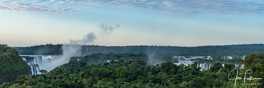 Iguazu National Park at sunrise with a plume of mist rising from the Devil's Throat.  The complex of falls extends for 2.7 kilometers with the  border between Brazil and Argentina passing through the Devil's Throat.  A UNESCO World Heritage Site.