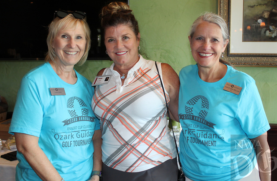 NWA Democrat-Gazette/CARIN SCHOPPMEYER Laura Jones (from left), Toni Luetjen and Laura Tyler, Ozark Guidance executive director help out at the Reinter Cup golf tournament.