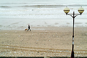 A man walks his dog along the beach in the Yorkshire seaside resort of Bridlington on Easter Bank Holiday.