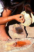 Koatinemo village, Brazil. Assurini Indian woman, Maye, decorating a pot with thin wooden split and ground rock paint.