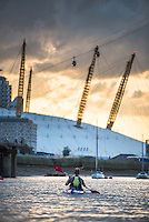 Kayaking on the River Thames at sunset by the O2 Arena, Greenwich, London, England