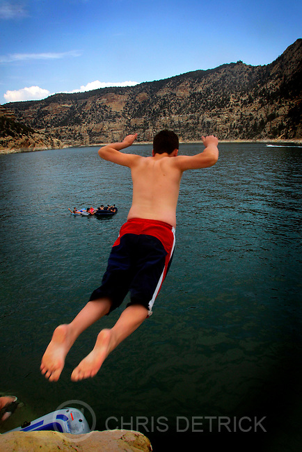 Flaming Gorge, UT--7/29/06-- Garrett Hansen, 12, of Evanston, WY, jumps off of a 20 foot rock into Flaming Gorge as family members watch from rafts in the water.