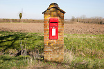 Scarlet red Post Office pillar box mounted in brick with fields in background, Hoo, Suffolk, England