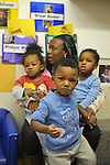 Teacher Francina Crayton, 35, holds (l-r) Aykil Millsapp, 1, and Arasia King, 2, while Brennan Emuwa, 1, stands in front in Room 123 at the Educare Early Childhood Center in Chicago on November 21, 2008.  The pre-K daycare center is a model for head start, funded privately by the Gates and other foundations, that cares for and educates infants, toddlers, and 3- and 4-year old pre-school children.