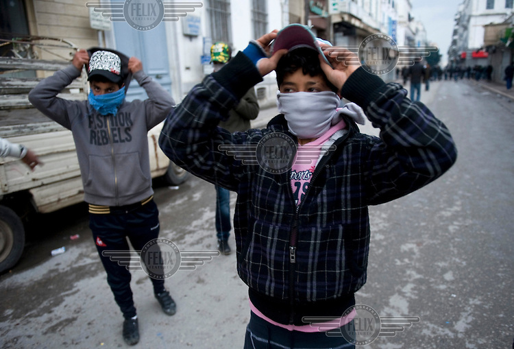Teenagers put on caps and hoods and wrap bandanas around their faces. Protests against former prime minister Mohamed Ghannouchi, who took control after the ousting of president Zine El Abidine Ben Ali, turned violent and left at least one dead and several wounded as soldiers used live ammunition and teargas against the protesters..