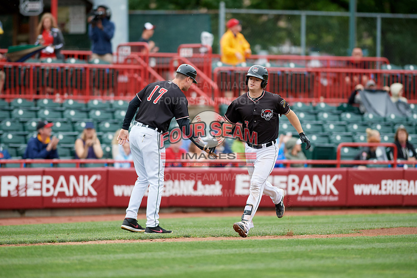 Erie SeaWolves catcher Jake Rogers (7) is congratulated by manager Andrew Graham (17) as he rounds third base after hitting a home run in the bottom of the fourth inning during a game against the New Hampshire Fisher Cats on June 20, 2018 at UPMC Park in Erie, Pennsylvania.  New Hampshire defeated Erie 10-9.  (Mike Janes/Four Seam Images)