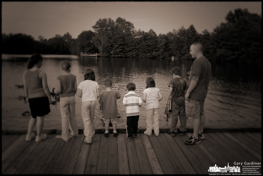 Brown toned, faded, old style photo of children at lake