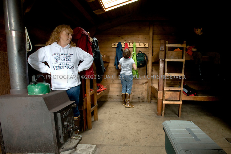 9/18/2008--Petersburg, Alaska, USA..From left to right: Shannon Peeler, Anne Volk and Tracey Kelly settle in at the Cascade Creek cabin in the Tongass National Forest. Reached in about 1 hour from nearby Petersburg, the cabin offers visitors easier access to the Alaskan wilderness without having to camp...Petersburg is on the north end of Mitkof Island, near the Tongass National Forest. A major fishing port, the town of 3500 is also a good jumping off point to see the Alaskan wilderness in south eastern Alaska. Petersburg can be reached on Alaskan Airlines via Seattle or nearby Juneau to the north...©2008 Stuart Isett. All rights reserved.