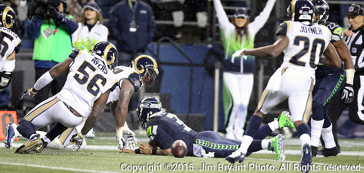 Seattle Seahawks quarterback Russell Wilson fumbles the ball while being tackled by St. Louis Rams defensive end Eugene Sims (97) at CenturyLink Field in Seattle, Washington on December 27, 2015.  The Rams beat the Seahawks 23-17.      ©2015. Jim Bryant Photo. All Rights Reserved