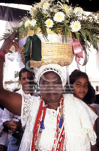 Salvador, Bahia, Brazil. Candomble follower in traditional white lace, beads carrying offering of flowers; Festival of Iemanja.