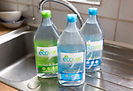 Plastic containers bottles of Ecover environmentally friendly washing-up liquid on kitchen window, England, UK
