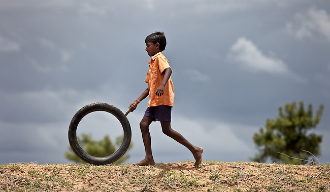 Mahanjesh (12) plays with a tyre in a fallow cotton field outside Bijanegere Village. Located outside of Raichur in Karnatarka, India the Government Primary and Secondary school in the village is benefitting from the IKEA Social Initiative, implemented in conjunction with UNICEF, by identifying child labourers and getting them out of working on farms and into school.Picture by Graham Crouch/UNICEF