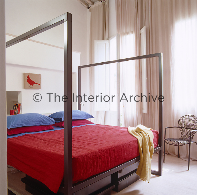 The double-height bedroom has a metal four-poster bed and floor-to-ceiling curtains