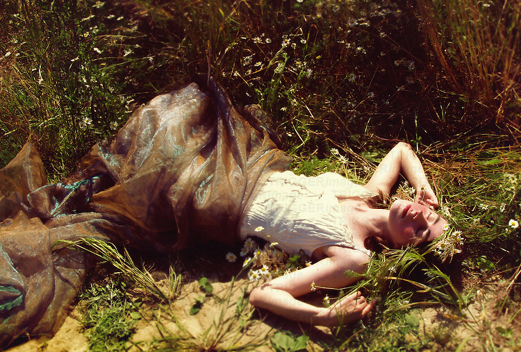 A woman dressed in vintage clothes, laying among flowers on a meadow, in a lazy sunbathing manner and her eyes closed.