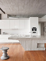 The spectacular kitchen is dominated by the central concrete island unit. The same material is used in the ceilings and walnut wood floors add warmth.
