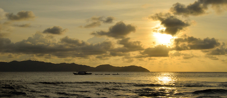 A local fishing boat passes the island of Komodo near sunset