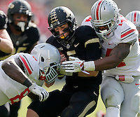 Ohio State Buckeyes defensive lineman Noah Spence (8) and Ohio State Buckeyes linebacker Curtis Grant (14) bring down Purdue Boilermakers quarterback Danny Etling (5) during the first half of the NCAA football game at Ross-Ade Stadium in West Lafayette, IN on Saturday, November 2, 2013. (Columbus Dispatch photo by Jonathan Quilter)