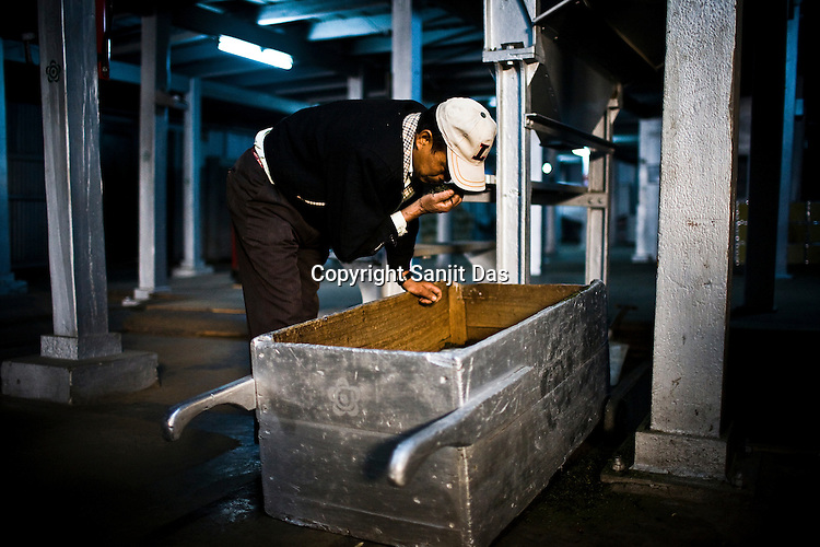 Niru Century, the factory supervisor, inhales the aroma of the first flush tea leaves after the drying process at the Makaibari Tea estate, in Darjeeling, India.