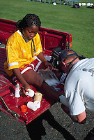 African-American female soccer player with ankle injury being wrapped in tape