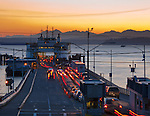 Seattle, WA<br /> Washington State Ferry Issaquah loading cars on the Fauntleroy ferry terminal, West Seattle - Olympic mountains in the distance at dusk