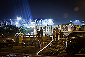 Residents of Delhi gather on the overpass to watch the laser lights preparations at the main stadium for the approaching 19th Commonwealth Games 2010 in New Delhi, India.