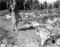 A German girl is overcome as she walks past the exhumed bodies of some of the 800 slave workers murdered by SS guards Namering, Germany, and laid here so that townspeople may view the work of their Nazi leaders.  May 17, 1945.  Cpl. Edward Belfer.  (Army)<br /> NARA FILE #:  111-SC-264895<br /> WAR & CONFLICT BOOK #:  1124