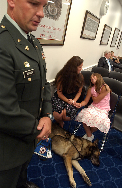 Army Chief Warrant Officer Thomas Burden is interviewed by the media as his wife Ari, as daughter Kyla Herringshaw, 9, sit with Ceaser, a medical alert dog that detects seizures in Mrs. Burden.   .Burden attended a news conference to talk about the risk facing soldiers who use predatory lenders.  The news conference was held to support a resolution sponsered by Rep. Sam Graves, which would limit interest rates on loans by so-called payday lenders, who target military personnel.