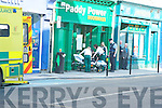 Ambulance staff and a Garda escort a man from Paddy Power Bookmakers to a waiting ambulance in Tralee on Thursday afternoon.