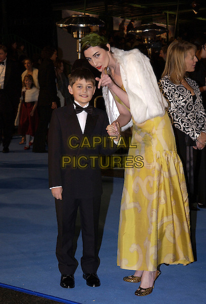 "ERIN O'CONNOR & GUEST.""The Chronicles of Narnia- The Lion, The Witch and the Wardrobe"".World film premiere, Royal Abert Hall.London England 7 December 2005.Ref: FIN.full length pointing gesture tuxedo white fur cape jacket yelow dress.www.capitalpictures.com.sales@capitalpictures.com.©Steve Finn/Capital Pictures"