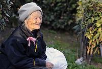 """Roma, 8 Marzo 2011.Piazza Vittorio.Manifestazione """"se non ora quando?""""per la dignità delle donne.Donna anziana con mimosa e fiocco rosa"""