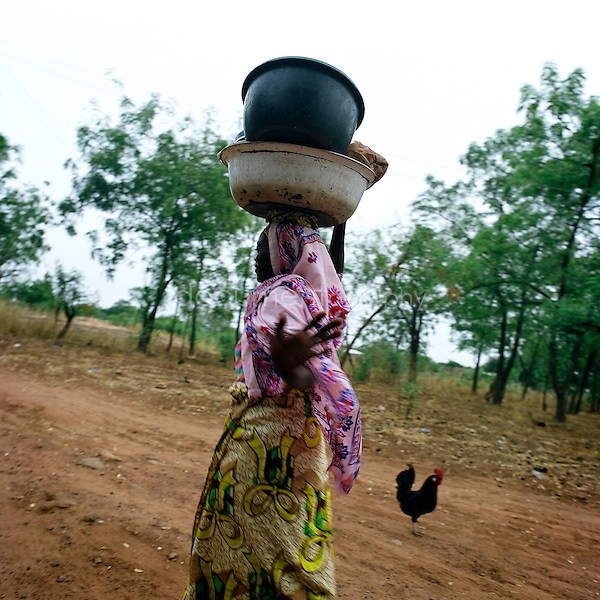 A woman going to the water well to collect water.