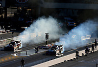 Sep 19, 2015; Concord, NC, USA; NHRA funny car driver Alexis DeJoria (left) does a burnout alongside Cruz Pedregon during qualifying for the Carolina Nationals at zMax Dragway. Mandatory Credit: Mark J. Rebilas-USA TODAY Sports